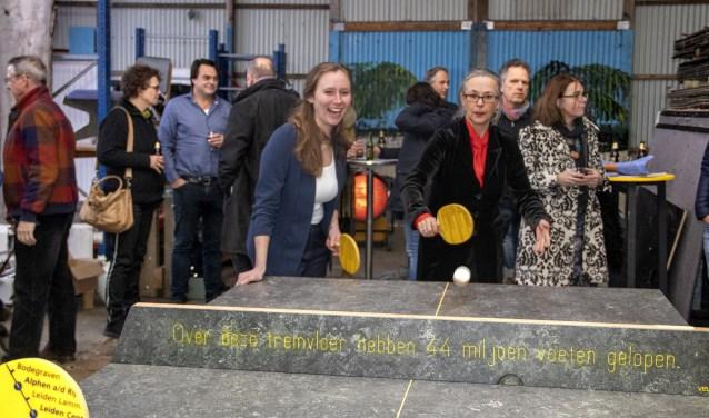 Gedeputeerde Zita Pels en NS Randstad-Noord directeur Irma Winkenius achter de tafeltennistafel gemaakt van hoogwaardige treinvloer.