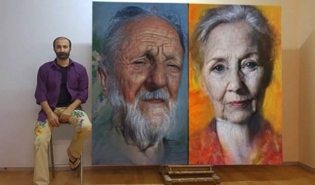 Araz Hama met twee van zijn schilderijen uit de serie Daklozen.