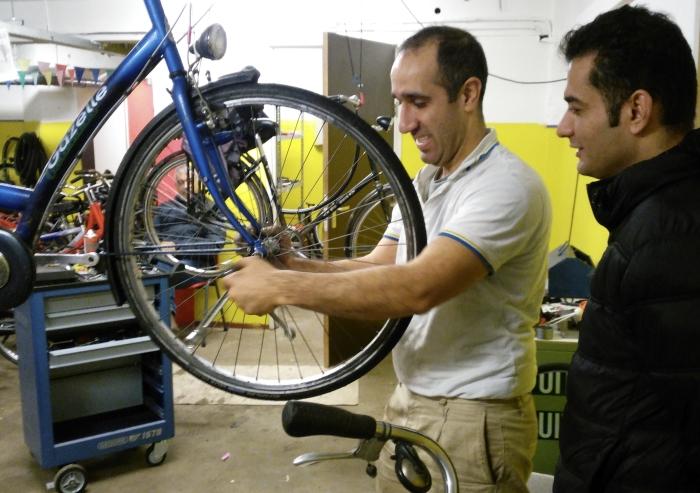 Fietsenmaker Hamidfreza is in de fietsenwerkplaats van het AZC in Leersum bezig met de fiets van een andere bewoner.