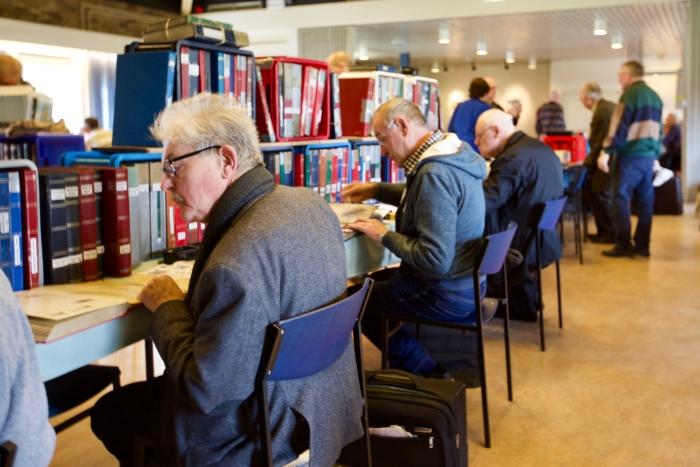 Verzamelaars die druk in de postzegelboeken aan het zoeken zijn naar nieuwe aanwinsten