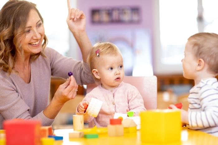 Een pedagogisch medewerker helpt kinderen op een leuke interactieve manier met de ontwikkeling van kinderen.