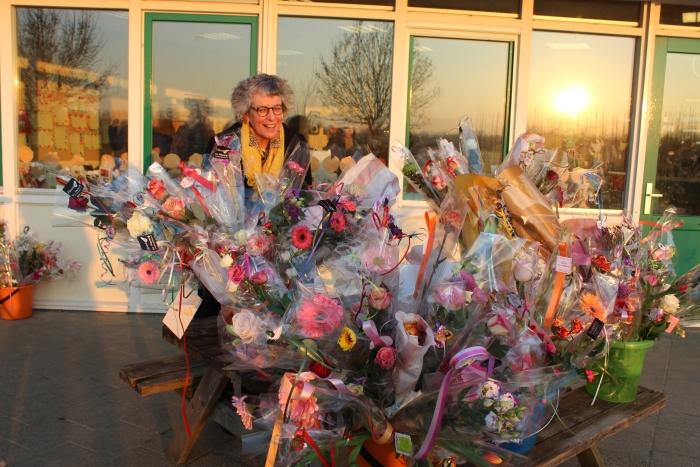 In het ochtendzonnetje wordt jubilerende juf Wilma ontvangen met héél veel bloemen! Mariëtte Koelewijn © BDU Media