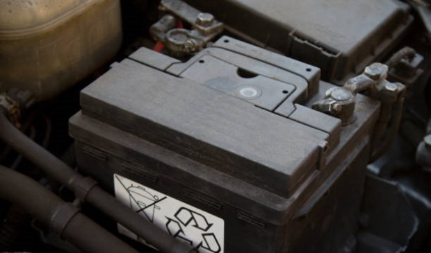 A car battery in place in an engine bay