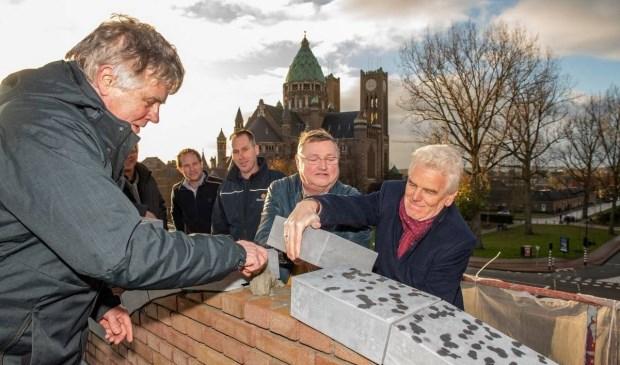 Tom van Hooijdonk (links) en Jan Aalbert (rechts) van Spaarnesant leggen de laatste steen van de Cruquiusschool.