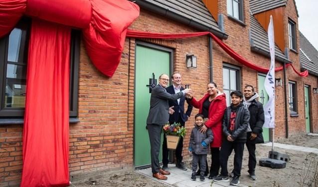 Remco Pols (Ymere) en Frits Lely (Van Wijnen) feliciteren de eerste huurders met hun nieuwe woning.
