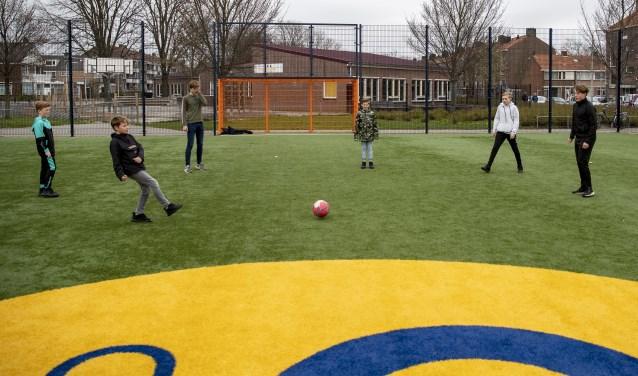 Kinderen aan het voetballen op een Cruyff Court in de tijd van Corona