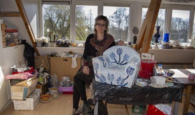 Annemarie Sybrandy in haar atelier in Heemstede met een kinderstoeltje, haar meest recente kunstwerk van mozaïek