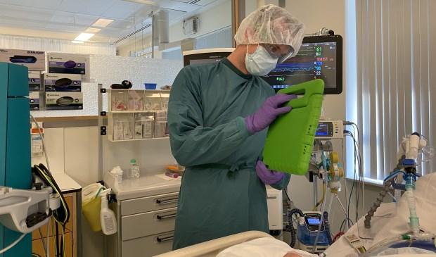 Een IC-verpleegkundige laat via beeldbellen aan familie zien hoe de patiënt in bed ligt