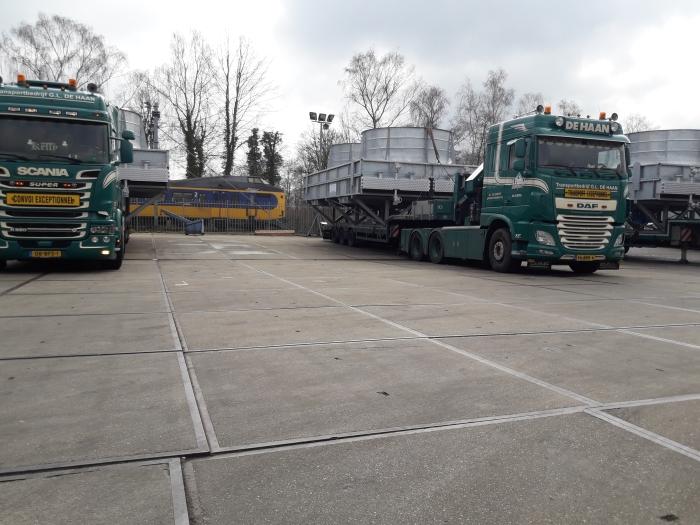 een paar van de beladen vrachtwagens tijdens het laden bij Bronswerk op het terrein