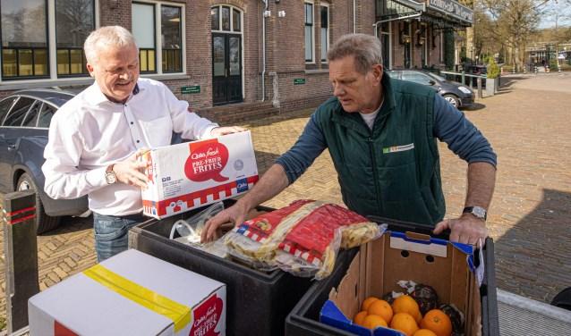 Ruud Bouwman (l) levert zijn voorraad in bij een medewerker van de Voedselbank.