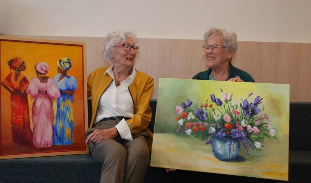 Ineke Bakker (links) en Joke Jansen met één van hun schilderijen die geëxposeerd worden in de bibliotheek.