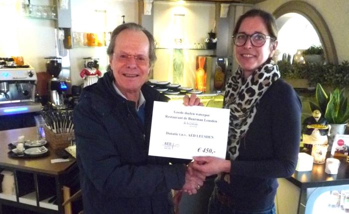 Jeff de Vries ontvangt de cheque voor een AED kast uit handen van Nadine Veeneman van restaurant de Buurman