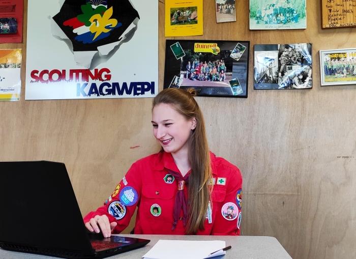 Vrijwilliger van de scouting. Achter een laptop. In het thema digitale opkomsten.