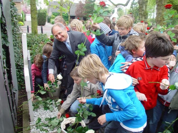Groep 8 leerlingen leggen op 17 april 2009, onder aanvoering van wethouder Bert de Graaf, witte en rode rozen bij het Walter Strang Monument.