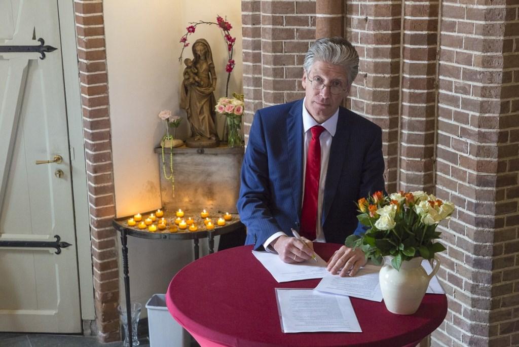 Secretaris van het parochiebestuur Hans ten Rouwelaar tekent het contract in de torenkapel van de Urbanuskerk. Dolf Middelhoff © BDU media