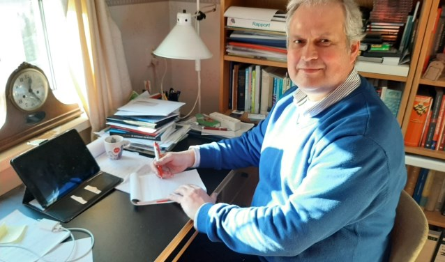 Wim Oosterwijk achter het bureau op zijn werkkamer.