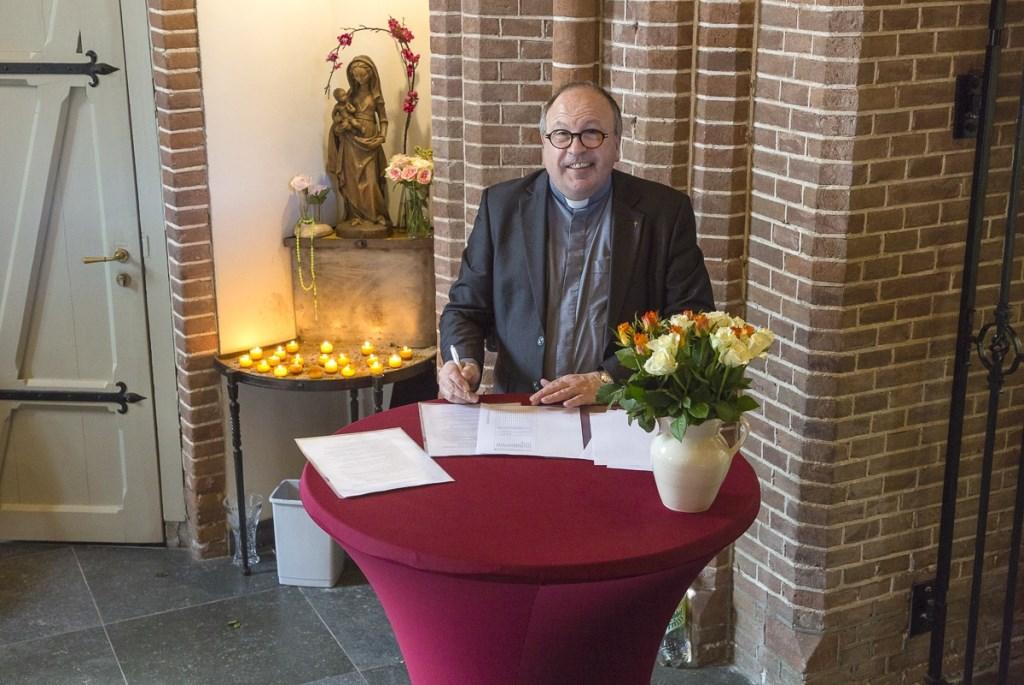Ook pastoor Eugène Jongerden tekent het contract. Dolf Middelhoff © BDU media