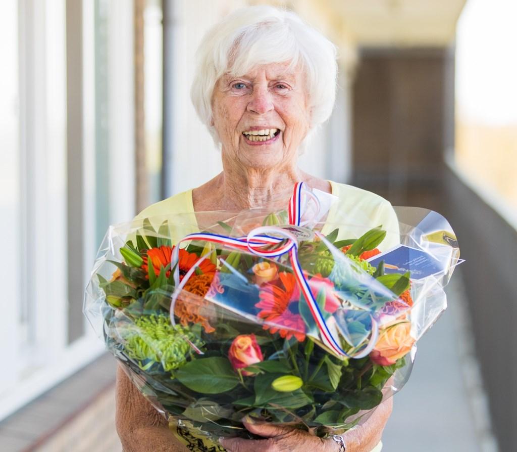 Annie van Dijk neemt haar bloemen in ontvangst.