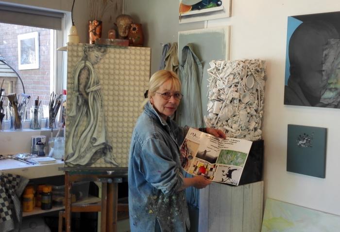 Organisator MAccc 2020 in haar atelier met affiche MAccc