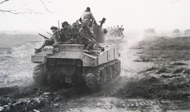 Bij de Ginkel: tanks met Britse infanterie onderweg over de hei naar Bennekom.