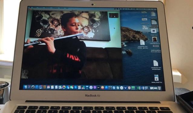 Dwarsfluitleerling Jort volgt online zijn muzieklessen.