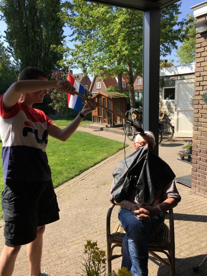 Opa zijn haar wordt op gepaste afstand eraf geschoren door kleinzoon Bas
