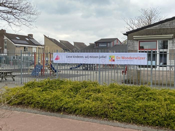 De banner aan het hek bij basisschool de Wonderwijzer