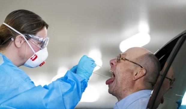 2020-04-06 15:26:01 ROTTERDAM - Een figurant bij een drive-in van een GGD testlocatie in Rotterdam. De 25 GGD'en beginnen met het testen van zorgmedewerkers die buiten de ziekenhuizen werken met patienten en coronaverschijnselen hebben. ANP ROBIN VAN LONKHUIJSEN