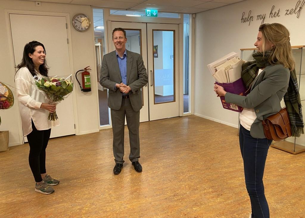 Wethouder Frank Berkhout en Marloes Smit geven directeur Bijlsma van de Linde een doos met Amstelkids.