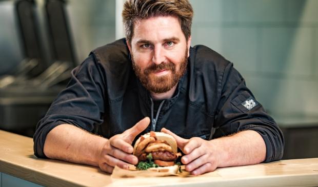 Henk van Keulen met een hamburger in de DINERfabriek.