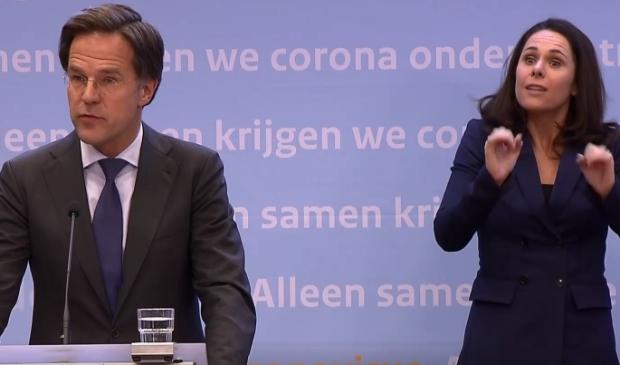 Mark Rutte en doventolk Irma Sluis tijdens de persconferentie waarbij de versoepeling van de maatregelen bekendgemaakt werd