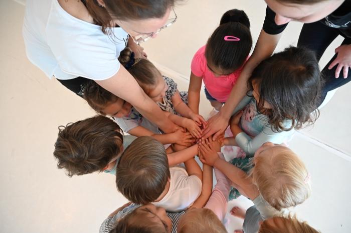 Samen doen waar je blij van word dansen. Kinderhanden op een stapel. Geen gezichten