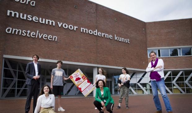 Wethouder Herbert Raat, Cobra-directeur Lillian Bóza, Stefan van Raay en enkele middelbare scholieren met de voucher voor het Cobra Museum.