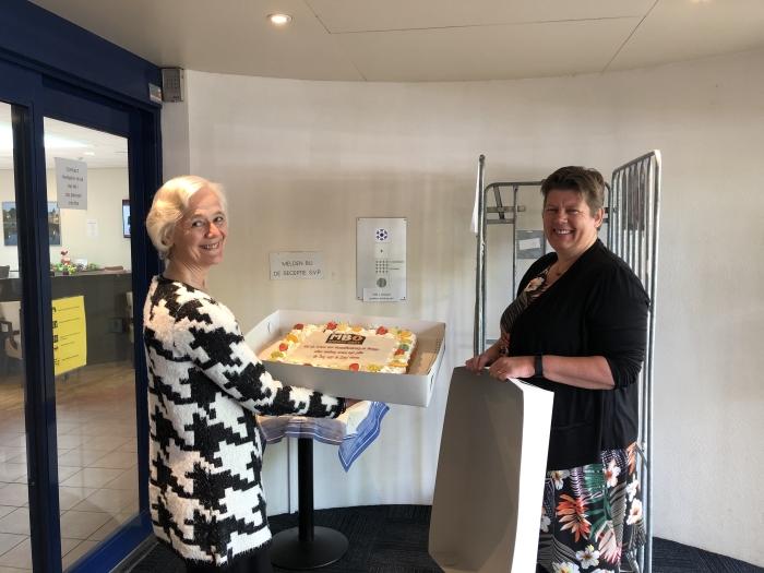 Yvonne Groot- Padberg, teamleider MBO Amersfoort, overhandigt de taart aan Mevrouw I.W.M. Vriens, bestuurder de Koperhorst.