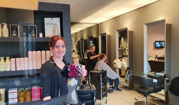 Renate Romeijn met op de achtergrond een collega die een klant behandelt. Iedereen is blij met de heropening.