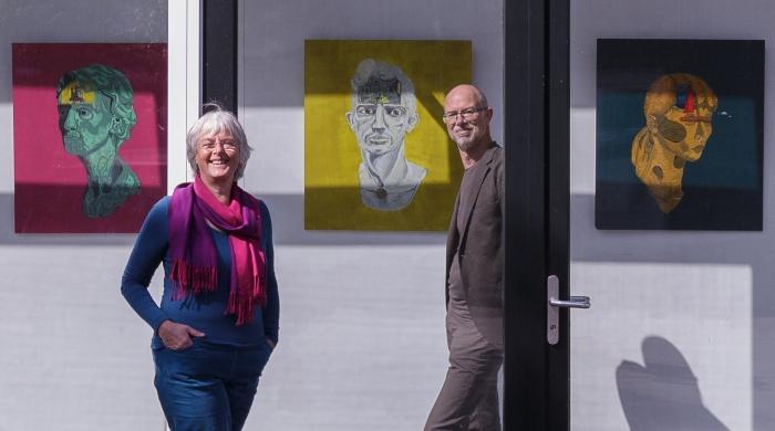 Emmy Bolsius en Anton Havelaar voor het werk van Nader Rikhtehgarchi. Op veilige afstand van elkaar, want gescheiden door glas.