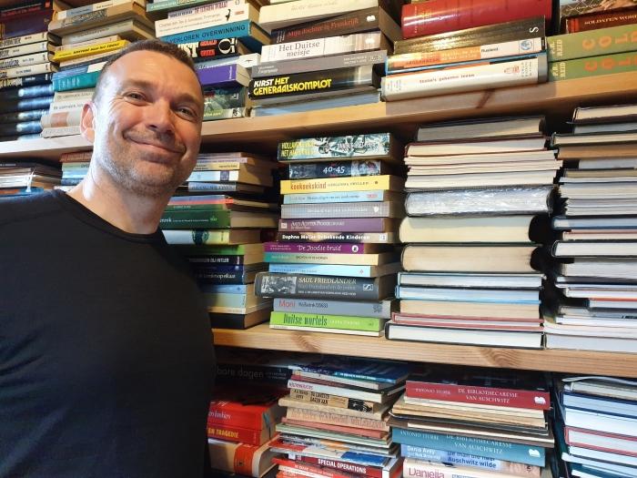 Huibert van Verseveld voor zijn verzameling boeken die te koop zijn op de boekenmarkt.