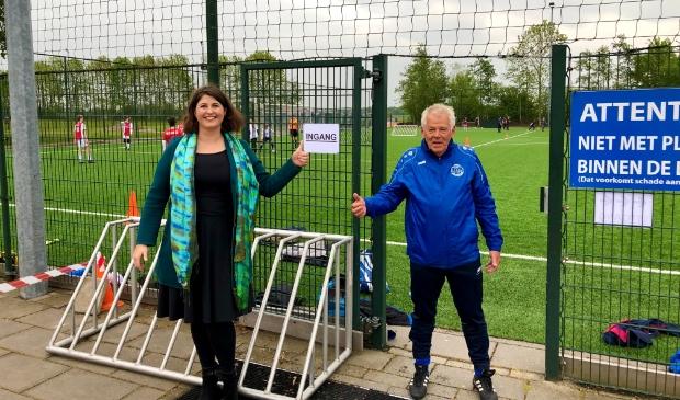 Wethouder Barbara de Reijke en jeugdtrainer Gerard Sieverding bij de ingang van een van de sportvelden.