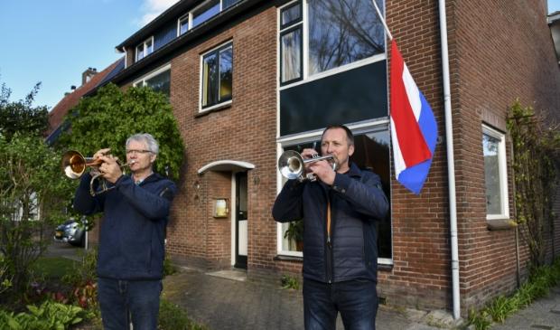 Leo en Adri Verlaan van PVO spelen The Last Post vanuit de tuin.
