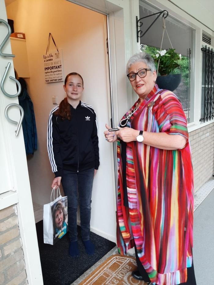 Jonge Mantelzorg Anouk krijgt een tasje aangeboden door Corry, medewerkster van Mantelzorg & Meer