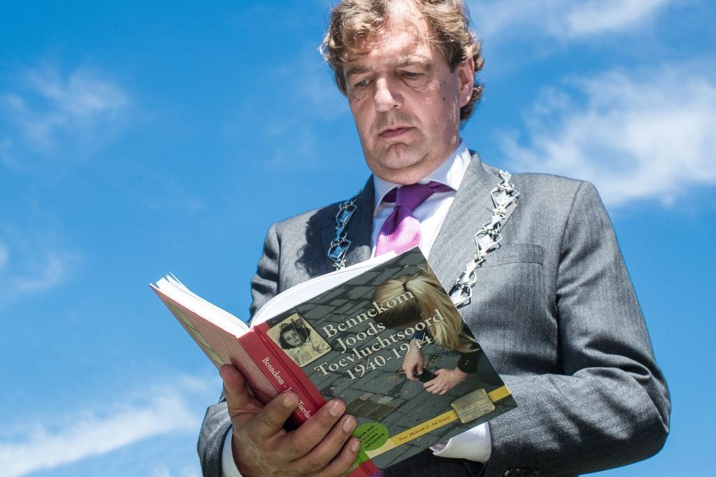 Burgemeester René Verhulst bekijkt het boek 'Bennekom Joods Toevluchtsoord 1940-1944' met linksboven op de voorpagina een foto van de 3-jarige Sara (Maartje). Ted Walker © BDU Media