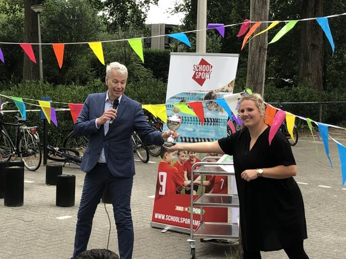 Wethouder Hans Buijtelaar overhandigt de stimuleringsprijs uit aan Deborah Drenth van basisschool De Windroos