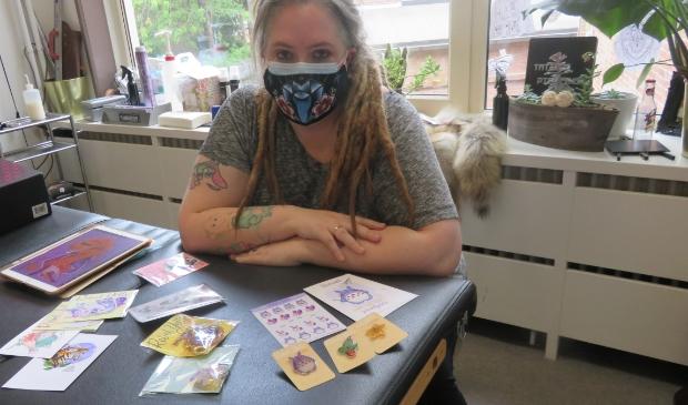 Saskia met een aantal in de vrije tijd door haar ontworpen spulletjes en het speciale mondkapje.