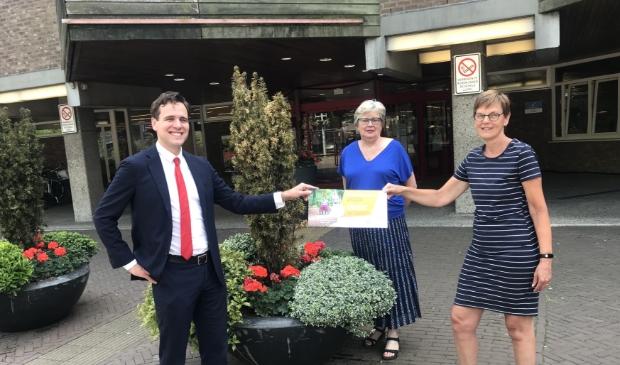 Carla van Houte en Maggy Wijffels overhandigen het eerste lot aan Wethouder Marijn van Ballegooijen.