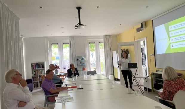 Op voldoende afstand luisteren de commissieleden naar uitleg van Annemiek de Hullu.