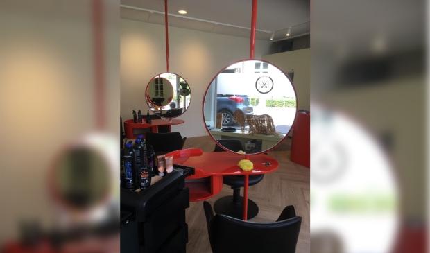 Bij binnenkomst springen de nieuwe rode, ronde spiegels en de rode kassa gelijk in het oog.