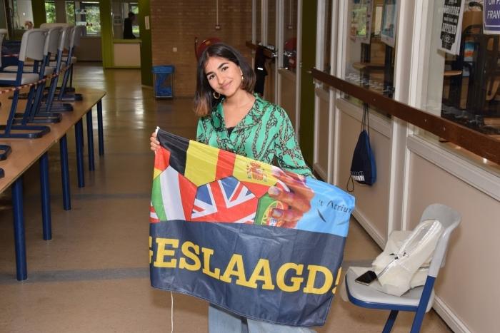 Een trotse leerling met haar welverdiende vlag.