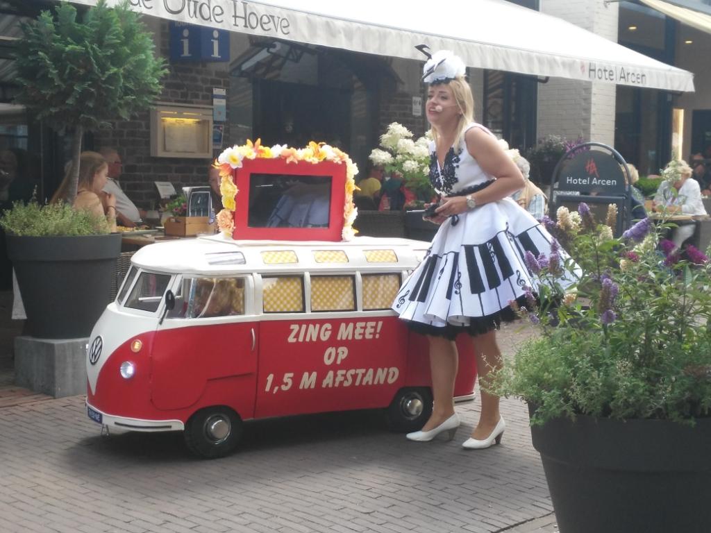 Tijdens een fietstocht in Arcen, kwamen we deze zangeres met muziekbus tegen. Zij bediende de bus op afstand en uit de bus kwam muziek. Iedereen kon meezingen en dat allemaal op afstand!  Truus Schoonderbeek-Kok © BDU media