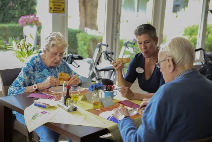 Bewoners van woonzorgcentrum Beatrix genieten samen met een medewerker van de versgebakken pizza. QuaRijn © BDU