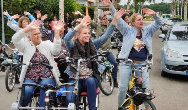 Juf Gerda Zwanenburg, links op de duofiets, swingt mee met collega's tijdens een optreden.